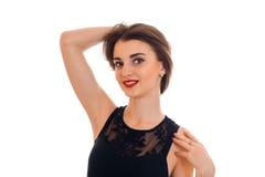 Portret van cutie jonge donkerbruine vrouw in modieuze zwarte kleding die die en de camera stellen bekijken op wit wordt geïsolee Stock Foto's