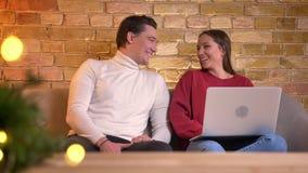 Portret van cyoung het donkerbruine meisje werken met laptop en het lachen met vriendenzitting naast haar op bank in huis stock video