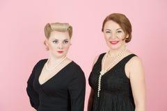 Portret van dames in zwarte kleding in Amerikaanse stijl op roze achtergrond royalty-vrije stock afbeeldingen