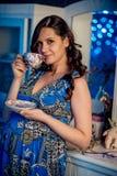 Portret van de aanbiddelijke jonge gelukkige zwangere vrouw met de donkere krullende kop thee van de haarholding thuis Royalty-vrije Stock Fotografie