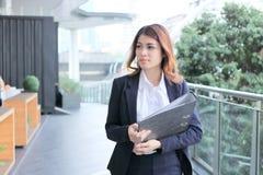 Portret van de aantrekkelijke jonge Aziatische onderneemster of secretaresseomslag van het holdingsdocument en het lopen in burea Stock Afbeeldingen