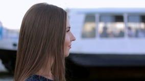 Portret van de aantrekkelijke jonge vrouw met lang recht haar op de achtergrond van de boot in de baai stock video