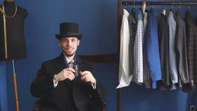 Portret van de aantrekkelijke mens in donkere laag en in kostuum binnen kleermakers stock footage