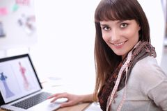 Portret van de aantrekkelijke vrouwelijke zitting van de manierontwerper bij bureau Royalty-vrije Stock Foto's