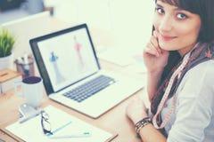 Portret van de aantrekkelijke vrouwelijke zitting van de manierontwerper bij bureau Stock Afbeelding