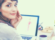 Portret van de aantrekkelijke vrouwelijke zitting van de manierontwerper bij bureau Royalty-vrije Stock Afbeelding