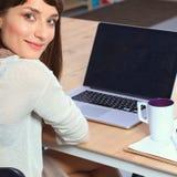 Portret van de aantrekkelijke vrouwelijke zitting van de manierontwerper bij bureau Stock Foto