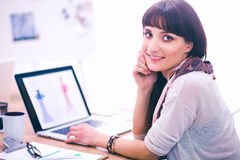 Portret van de aantrekkelijke vrouwelijke zitting van de manierontwerper bij bureau Royalty-vrije Stock Afbeeldingen