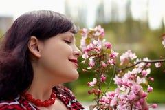 Portret van de aardige jonge vrouw met een tot bloei komende tak Royalty-vrije Stock Afbeelding