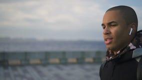 Portret van de Afrikaanse Amerikaanse mens die in modieuze oortelefoons op stedelijke dijk lopen stock footage