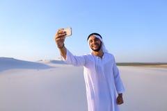 Portret van de Arabische sjeikmens met gadget dat binnen communiceert Stock Afbeelding