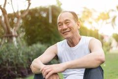 Portret van de Aziatische hogere mens die en op gras bij Th ontspannen zitten Stock Fotografie