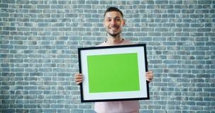 Portret van de blije mens die onecht omhoog groen het schermbeeld op baksteenachtergrond dragen stock footage