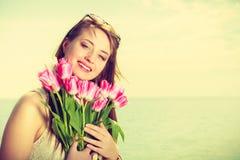 Portret van de bloemen van de vrouwenholding op strand royalty-vrije stock afbeeldingen