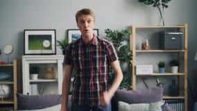 Portret van de boze jonge en mens die uitdrukkend sterke negatieve emoties schreeuwen gesturing die zich in modern huis bevinden  stock footage