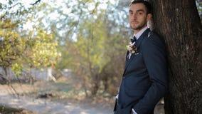 Portret van de bruidegom Jonge mens dichtbij de boom stock footage
