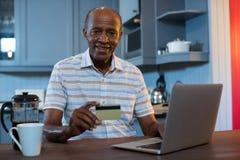 Portret van de creditcard van de mensenholding terwijl het gebruiken van laptop Stock Foto's