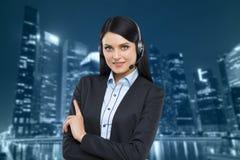 Portret van de donkerbruine exploitant van de steuntelefoon met de hoofdtelefoon Stock Afbeeldingen