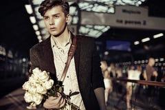 Portret van de elegante jonge kerel met bloemen stock foto