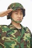 Portret van de ernstige jonge mens in het militaire eenvormige groeten, studioschot Royalty-vrije Stock Foto