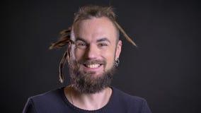 Portret van de freaky Kaukasische mens met dreadlocks en het doordringen tonend positief vermaak en geluk op zwarte stock video