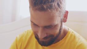 Portret van de gebaarde volwassen mens in geel overhemdsspel in spel op tablet Glimlach stock videobeelden