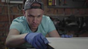 Portret van de geconcentreerde man in GLB, betrokken bij zijn werk De gloved arbeider die en zijn diy controleren meten stock videobeelden