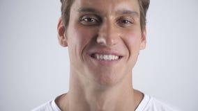 Portret van de geglimlachte knappe man die en aan de camera op de witte muurachtergrond glimlachen kijken Sluit omhoog binnen stock footage