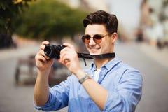 Portret van de gelukkige jonge mens, toeristen met camera in de nieuwe stad stock fotografie