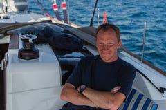 Portret van de gelukkige mens op zijn varende jachtboot op het overzees De zomer royalty-vrije stock afbeelding