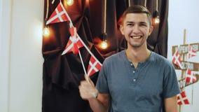 Portret van de gelukkige reizigers jonge mens die Deense vlag, het golven en het glimlachen het bekijken camera houden stock videobeelden