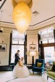 Portret van de gelukkige zitting van het jonggehuwdepaar op modieuze luxueuze achtergrond met massieve gele glans Stock Afbeeldingen