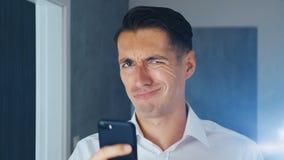 Portret van de geschokte en weerzinwekkende mens De verwarde mens zag een onplezierig bericht op een smartphone Hij is ongerust g stock video