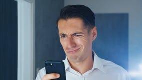 Portret van de geschokte en weerzinwekkende mens De verwarde mens zag een onplezierig bericht op een smartphone, in verrassing st stock video