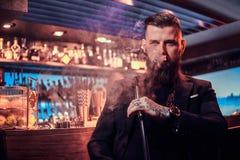 Portret van de getatoeeerde gebaarde mens dat waterpijp rookt, makend aardige damp royalty-vrije stock foto