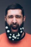 Portret van de gillende jonge gebaarde hipstermens met bloemen Stock Afbeeldingen