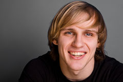 Portret van de glimlachende blonde mens over grijze achtergrond Royalty-vrije Stock Afbeelding