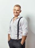 Portret van de glimlachende jonge mens in witte overhemd en bretels royalty-vrije stock foto's