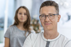 Portret van de glimlachende mens met dochter status op achtergrond thuis Stock Afbeeldingen