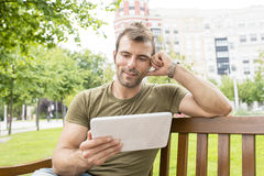 Portret van de glimlachende toevallige mens die tabletcomputer in st kijken royalty-vrije stock fotografie