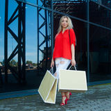 Portret van de glimlachende vrouw van de schoonheidsmanier met het winkelen zakken in rood overhemd dichtbij winkelcentrum openlu Royalty-vrije Stock Foto's