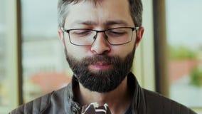 Portret van de hongerige gebaarde mens die de lollie van het chocoladeroomijs eten stock footage