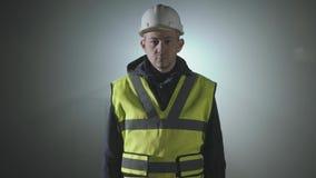 Portret van de ingenieur in de bouwers eenvormig en helm op een zwarte achtergrond in de schijnwerper op het werk stock video