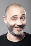 Portret van de ironische glimlachende die mens op grijs wordt geïsoleerd Stock Foto
