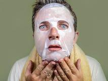 Portret van de jonge bizarre en grappige mens die thuis binnen gebruikend schoonheidsdocument gezichtsmasker het reinigen het ler royalty-vrije stock foto's