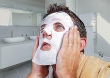 Portret van de jonge bizarre en grappige mens die thuis binnen gebruikend schoonheidsdocument gezichtsmasker het reinigen het ler stock foto