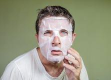 Portret van de jonge bizarre en grappige mens die thuis binnen gebruikend schoonheidsdocument gezichtsmasker het reinigen het ler royalty-vrije stock foto