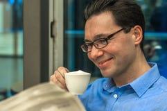 Portret van de jonge donkerbruine zitting van de haarzakenman in een koffie royalty-vrije stock fotografie