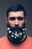 Portret van de jonge gebaarde hipstermens met bloemen Royalty-vrije Stock Foto's