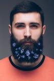 Portret van de jonge gebaarde hipstermens met bloemen in zijn baard Royalty-vrije Stock Afbeelding